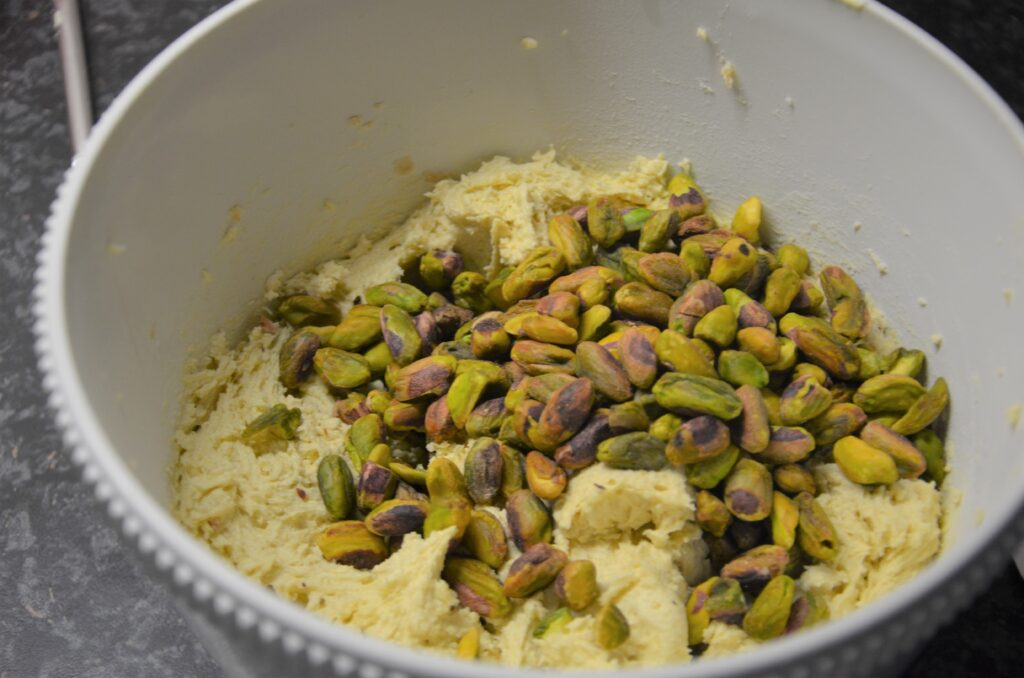 Adding the pistachios to the dough, in a white bowl