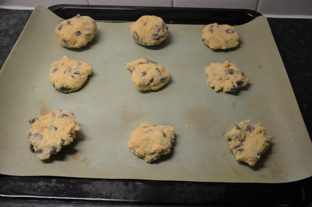 Oreo stuffed and regular chocolate chip cookies before baking them lined out on a baking sheet 3 rows of 3