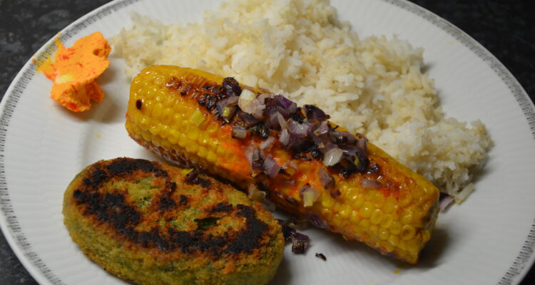 Grilled corn on the cob with bell pepper butter, rice and a rondo on a white plate