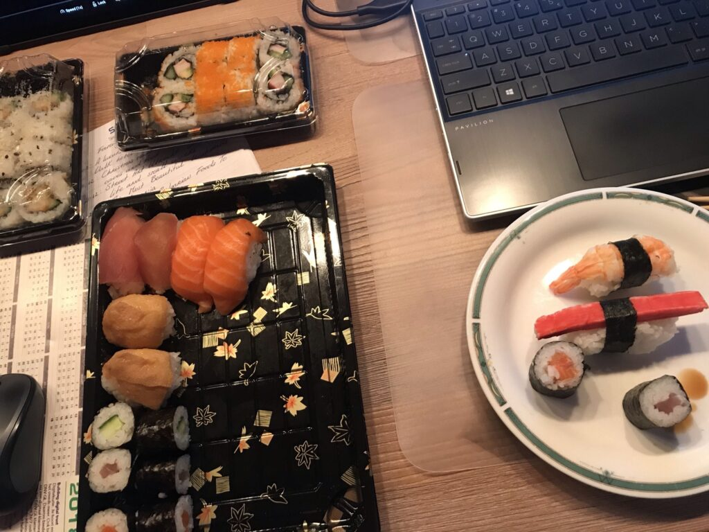 Sushi, some on a small plate, the rest still in boxes, one box is opened. A laptop on the side. Week 2 2021