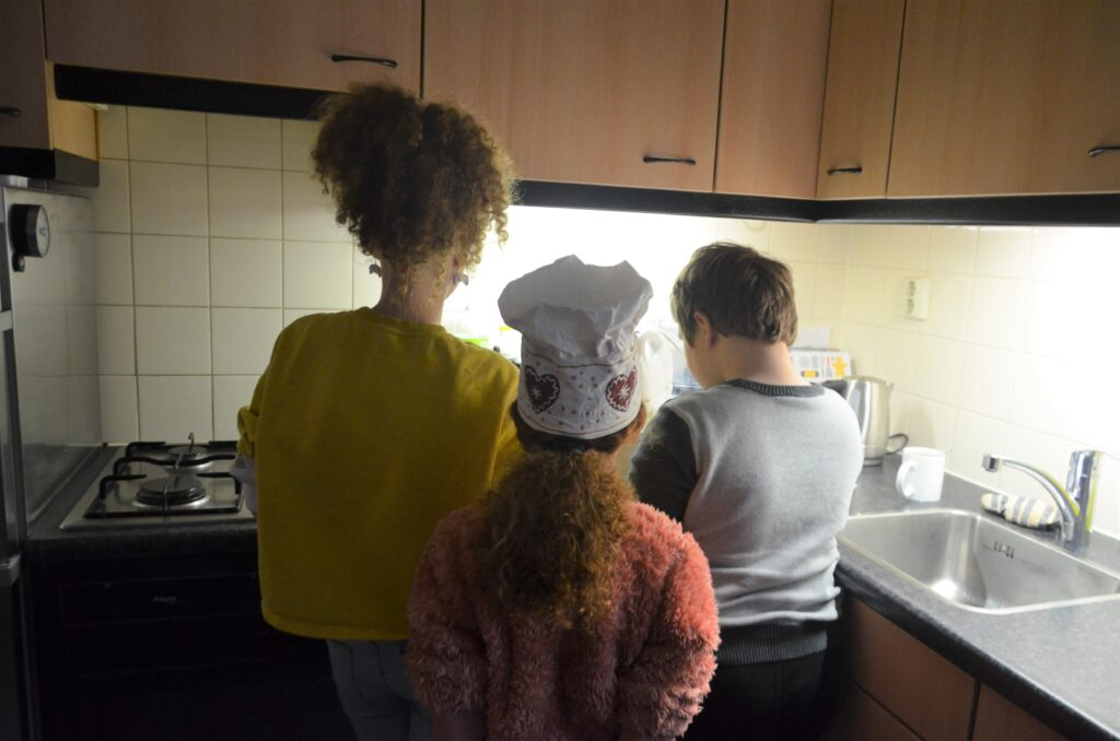 Yuri and his nieces in the kitchen, seen from behind.