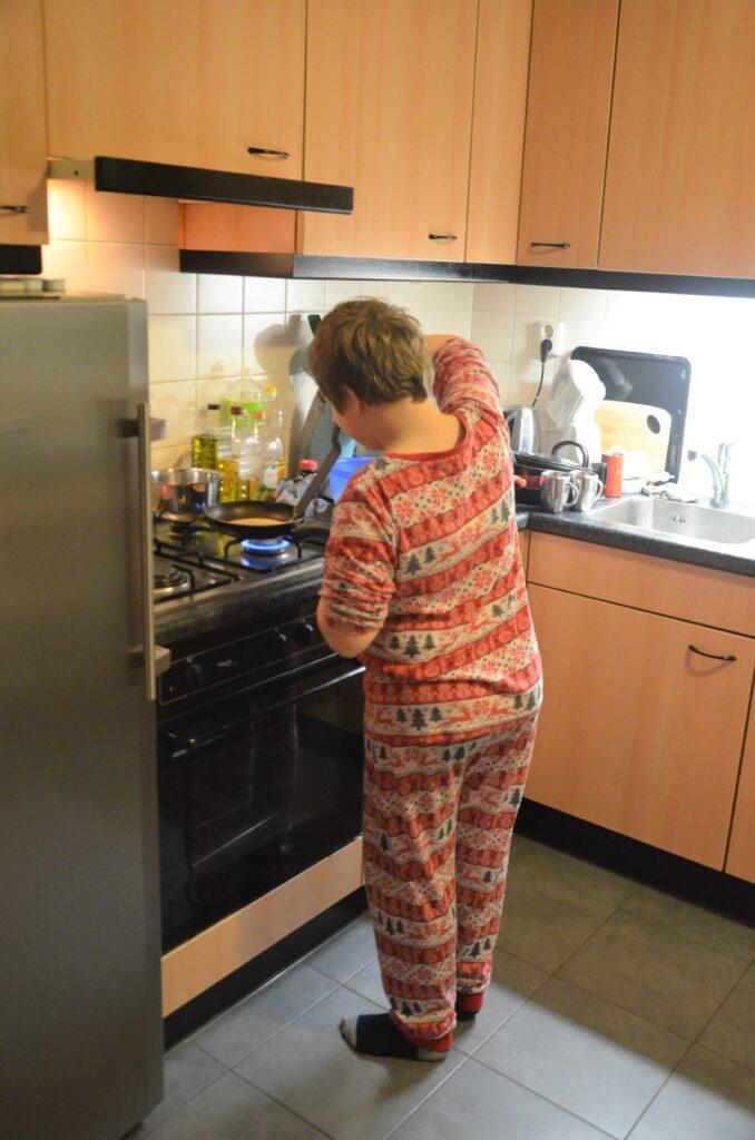 Yuri baking pancakes, flipping a pancake
