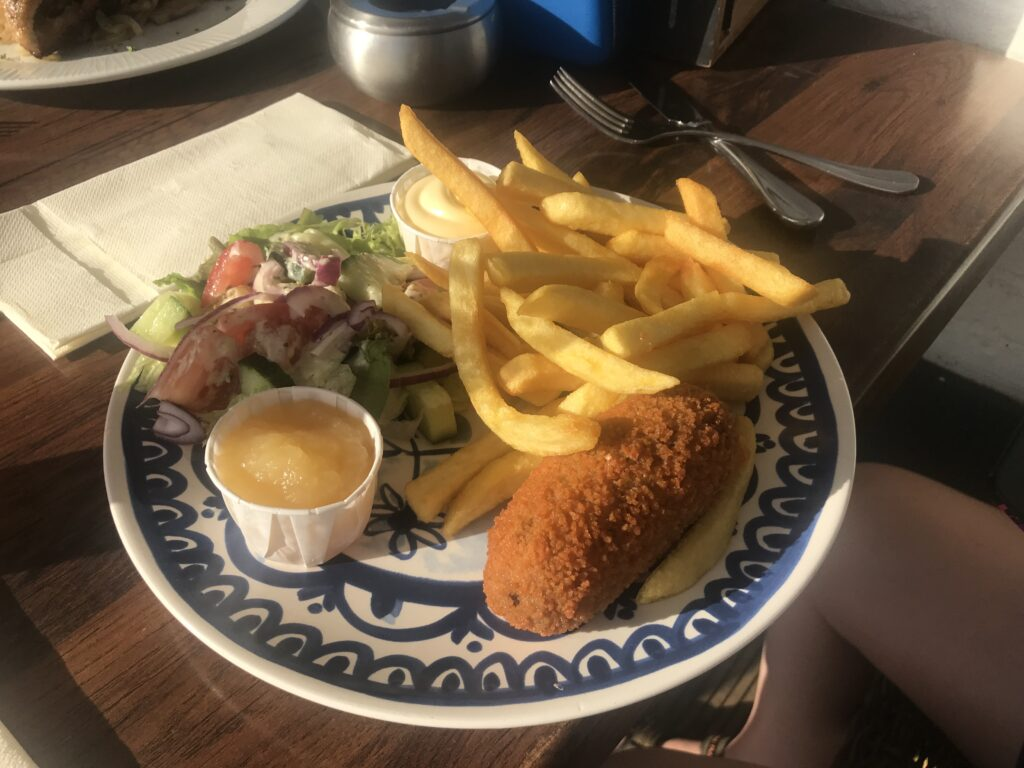 A Kroket for dinner on a blue and white plate with apple sauce, fries and salad on the plate