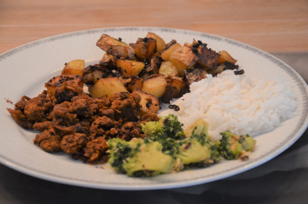 Broccoli with coconut, rice, vega ground meat and potatoes on a white plate from the side