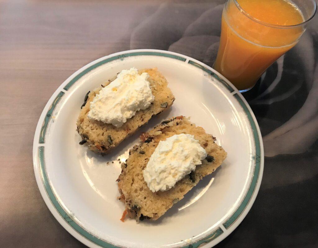 Brioche with whipped cream and orange juice, brioche on a white plate
