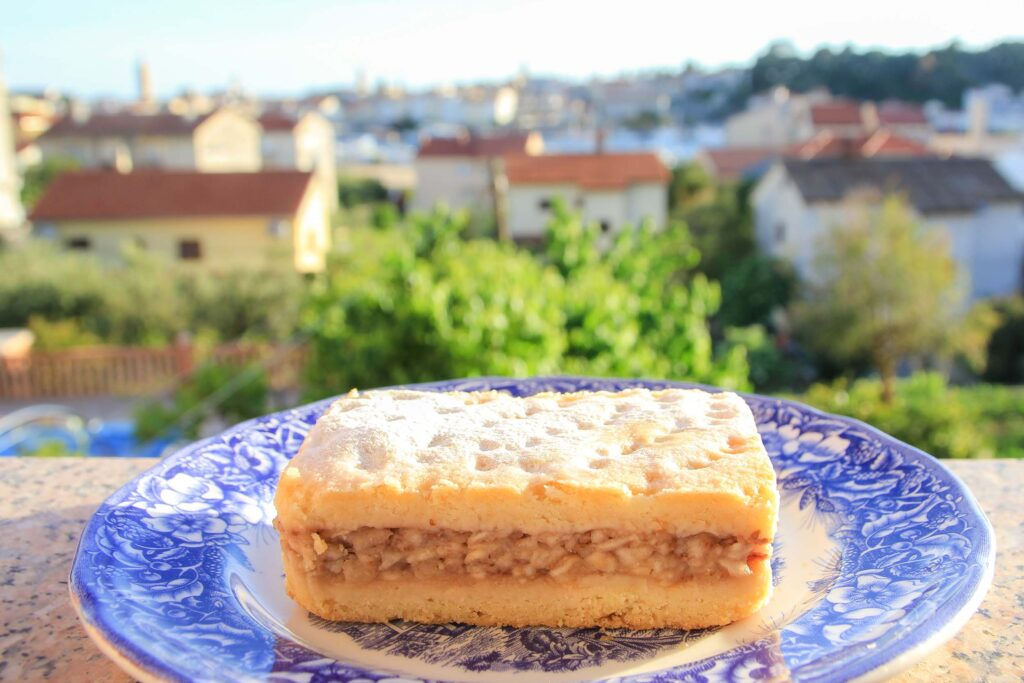 Croatian Apple Pie by Jürgen Reichenpfader, a rectangle apple pie piece on a plate, with a nice view behind it