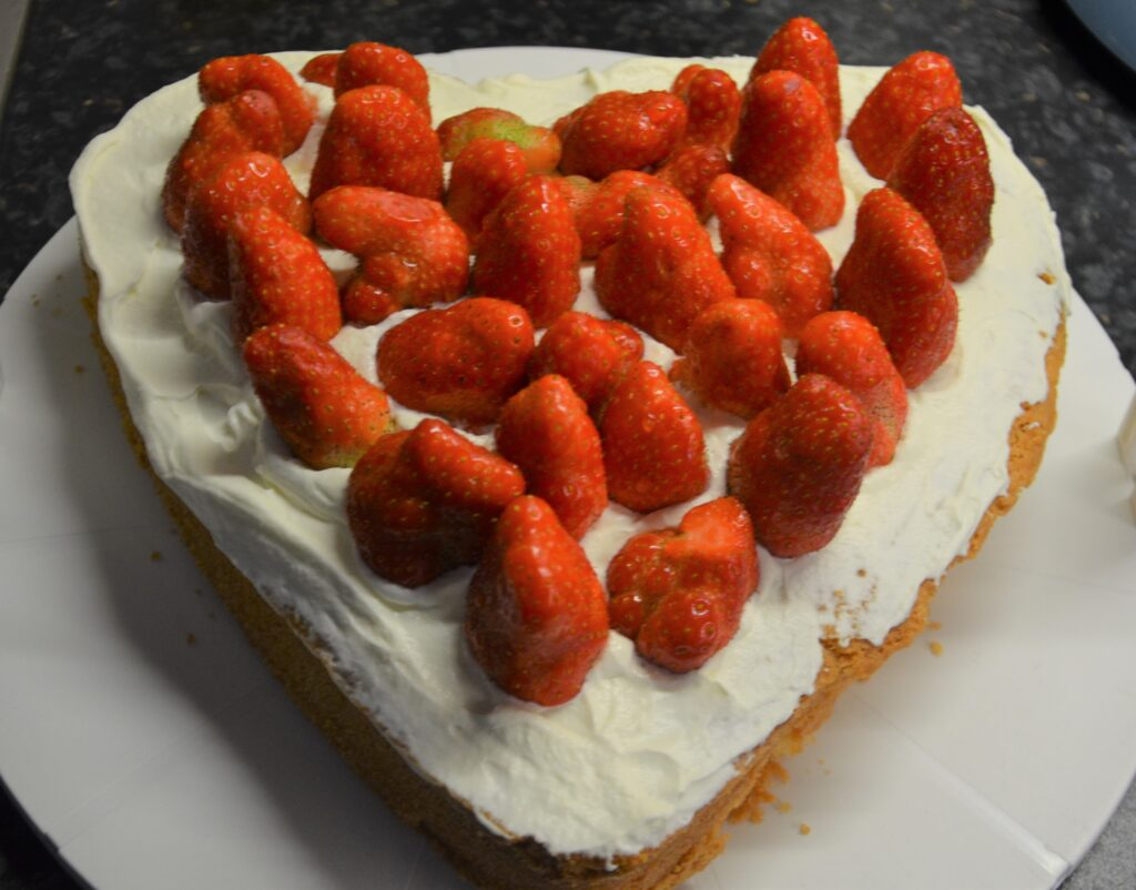 Mother's Day Cake, a heart shaped cake topped with whipped cream and strawberries, presented on a flat plateau.