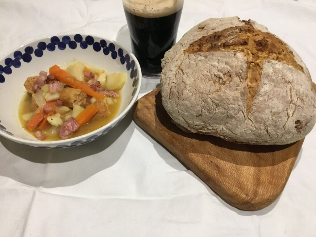 Irish Soda Bread & Coddle by Map Made Memories, soda bread on the right on a wooden board, the coddle in a bowl on the left, with a pint of guinness behind it. On a white cloak