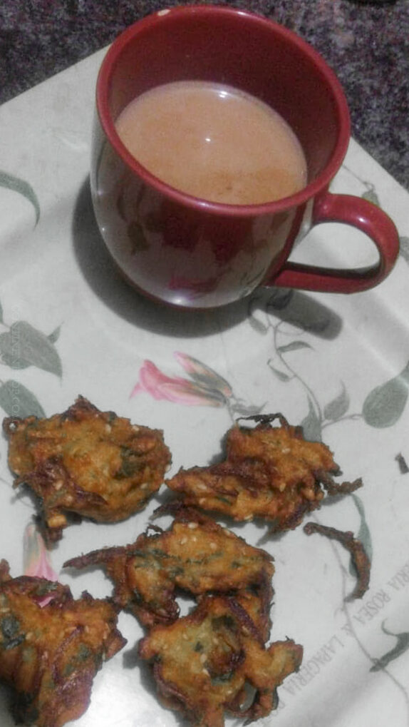 Onion Bhajji by Continent Hop, , about 3 bhajji are laying on the table, to the left a cup of coffee