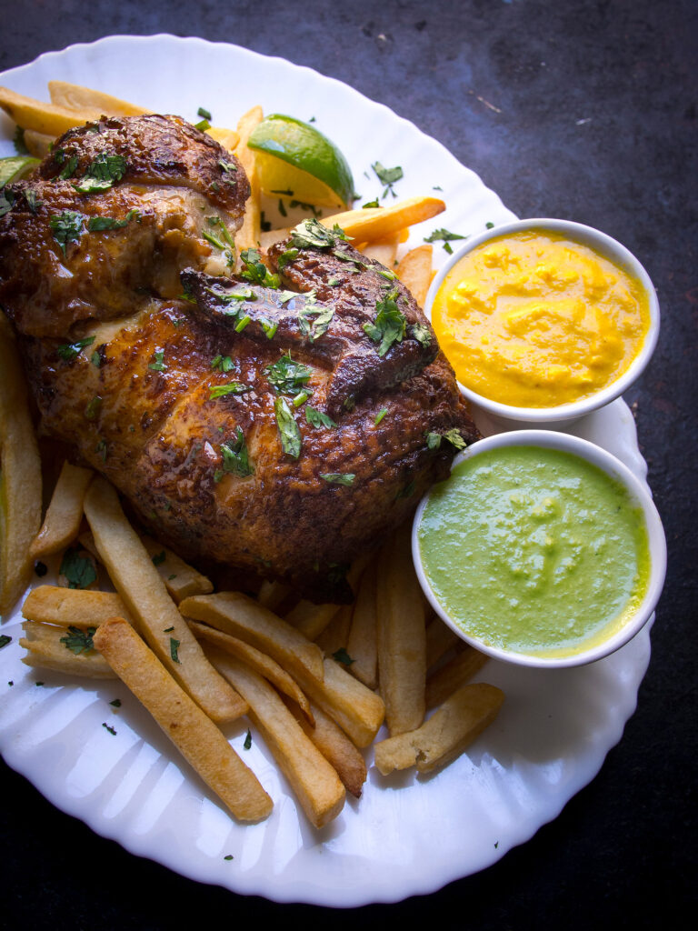 Peruvian Chicken by Bacon is Magic, the chicken on the upper left, with fries under it to the left, on a white plate, with 2 small bowls with a yellow and a green sauce on the right on the plate
