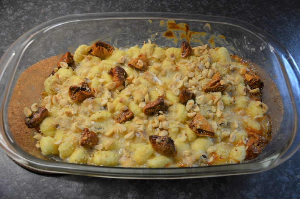 A casserole dish with creamy gnocchi recipe with dolcelatte, figs and hazelnuts in it. Just out of the oven