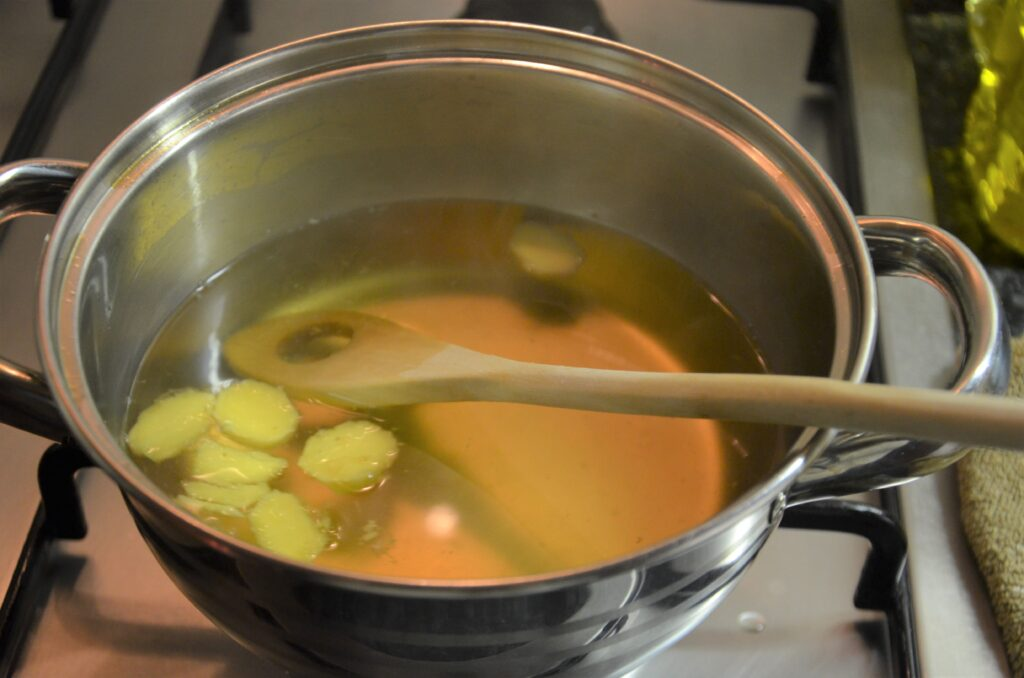 Ginger with water and apple vinegar in a pan on the stove