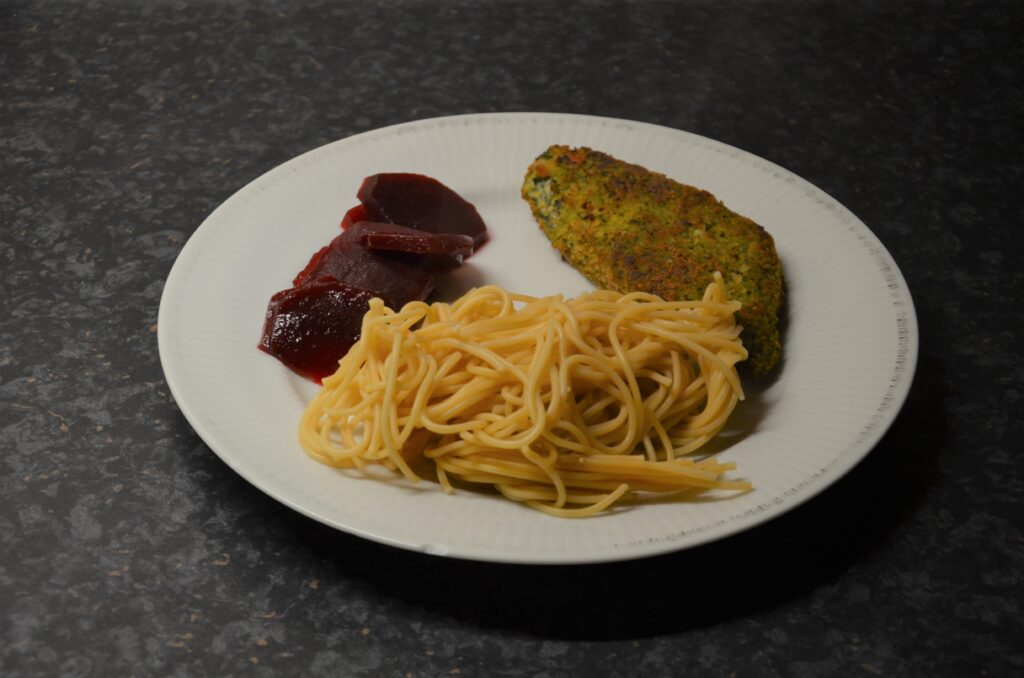 Sweet and Sour Red Beets with spinach-cheese schnitzel and spaghetti on a white plate