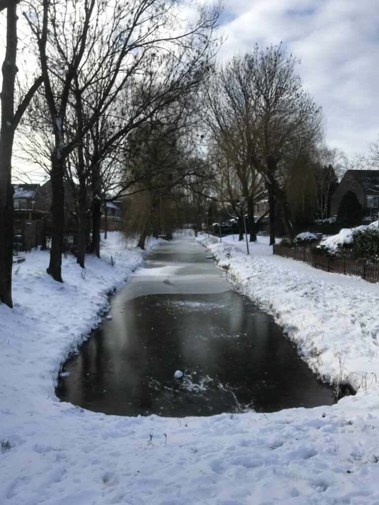 Snowy Lunetten, a lightly frozen creek, with snow covered banks on the side