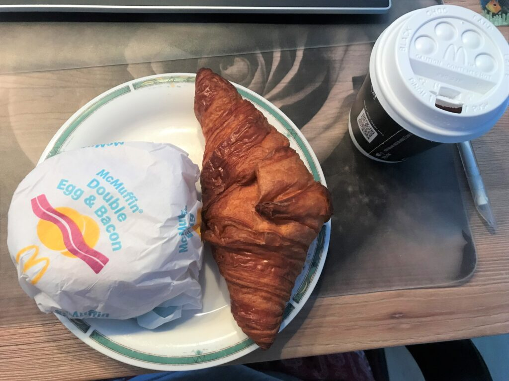 McDonald's Breakfast, a croissant and a burger in paper wrap  on a white plate and a tea on the side