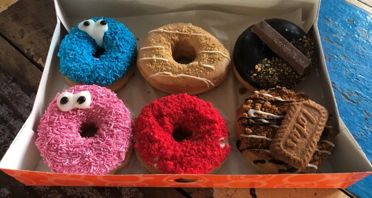 Donut Box Dunkin' Donuts with 6 different donuts in it. From left to right and top, starting in the top. Blue Cookie Monster, maple, kitkat, pink cookie monster, red velvet and speculoos